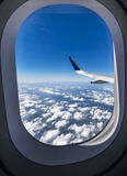 View through the window of a passenger plane flying above beauti. Ful white clouds in to the sky Royalty Free Stock Photo