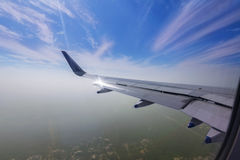 View through the window of a passenger plane flying above the ci Royalty Free Stock Image