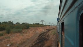 View from the window of the passing train. View from the window of a train passing through a field. Shooting from the train window. Traveling in a train. Railway stock footage