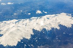 View from the window of the plane that flies over the mountains royalty free stock photography
