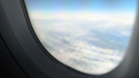 View through window of plane flying above clouds in peaceful sky, air transport. Stock footage stock video
