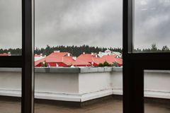 The view from the window on the red roofs of houses and forest
