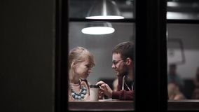 View through the window. Romantic date of young beautiful couple. Attractive man and woman sitting in the cafe. View through the window. Romantic date of young stock video footage