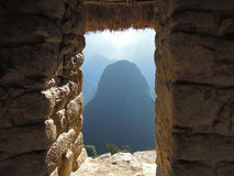 View through a window of the ruins in Machu Picchu Peru. MACHU PICCHU, PERU MAY 30 2012: View of the surrounding mountains through a window of the Machu Picchu royalty free stock photo