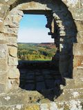 View through a window of the ruins of Skelton Tower. Near Levisham on a bright, sunny autumn day with views over North York Moors National Park, Yorkshire, UK Stock Image