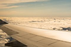 View from the window seat of a plane above the cloud. Ier the wing royalty free stock photo