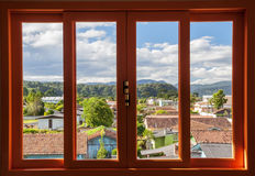 View through a window. View of a small town through a window with red frame in Urubici, Brazil Stock Photos
