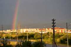 View from the window to the industrial street. Rainbow after rain. Sun and dark Royalty Free Stock Images