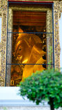 View on window to Reclining Buddha gold statue in hall Stock Photos