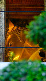 View on window to Reclining Buddha gold statue in hall Royalty Free Stock Photography