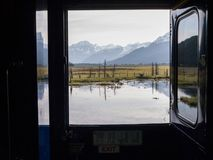 View from window of train in Alaska with pond, field and snowcapped mountains beyond stock photography