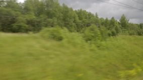 The view from the window of the train car. Rails, landscape, trees, summer sunny day. Filming from the window of a moving train. Summer sunny day, forest, power stock video