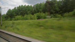 The view from the window of the train car. Rails, landscape, trees, summer sunny day.  stock footage