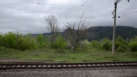 The view from the window of the train on the rails and the verdant mountains in the distance on a background of white clouds. Cauc stock video footage