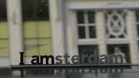 View through the window of tram in Amsterdam. Traveling in the city by public transport. View through the window of bus or tram with focus on slogan I amsterdam stock video footage