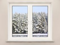 Photo of Window with Forest View.. View through the window on the snow-covered forest on wall in the room, photo Royalty Free Stock Photos