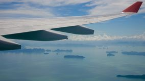 View from the window of an airplane flying over the sea with tropical islands stock footage