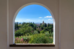 View through a window in the world-famous Alhambra. In Granada with beautiful views of the fortress and Granada stock image
