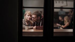View through the window. Young beautiful couple sitting in the cafe and talking. Romantic date in downtown in evening. Happy man and woman enjoying time stock video footage