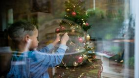 View through a window of a young boy decorating Christmas tree royalty free stock photo