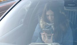 View through windshield of the car on young brunette woman in blue down jacket looking at the phone. stock image