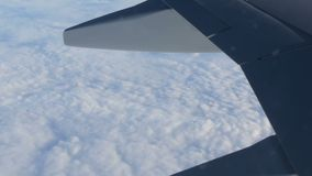View of the wing of an airplane in flight over beautiful air clouds. A view of the wing of an airplane in flight over beautiful air clouds stock footage