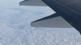 View of the wing of an airplane in flight over beautiful air clouds. A view of the wing of an airplane in flight over beautiful air clouds stock video footage