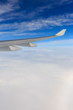 A view of wing of airplane from window above clouds and blue sky Royalty Free Stock Photo