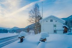 View of winter road snow and ice with some wooden boxes close to a wooden white house, covered with snow at one side of. The road in Norway stock photo