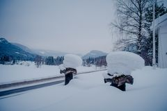 View of winter road snow and ice with some wooden boxes, covered with snow at one side of the road in Norway.  royalty free stock photo