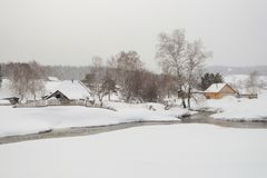 View of the winter village where. There is a lot of snow and a stream Royalty Free Stock Photography