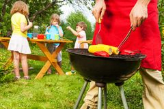 View of woman in apron fragment grilling corn Stock Photo