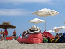View at Woman from Back Lying on Red Pillow Cushion and Relaxing on Ocean Sand Beach Wearing Straw Hat During Summer Vacation royalty free stock image