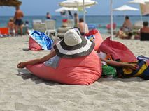 View at Woman from Back Lying on Red Pillow Cushion and Relaxing on Ocean Sand Beach Wearing Straw Hat During Summer Vacation stock images