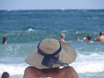 View at Woman from Back Wearing Straw Hat on Ocean Beach During Summer Vacation stock photos