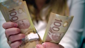 View of a Woman Counting Many Canadian 100 Bills stock video footage