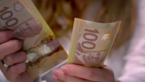 View of a Woman Counting Many Canadian 100 Bills stock footage
