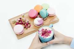 View on woman hands holding a blue cappuccino cup and beauty french macarons Royalty Free Stock Photography