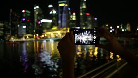 Singapore phone photo. View of woman`s hands taking photo on mobile phone camera of Singapore marina and financial district skyline. Hand touching and holding stock video