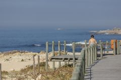 View of woman seat on wood bench in pedestrian wooden walkway, beach and sea as stock photos
