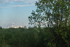 View from the wood on pipes of pulp and paper mill. Concept of ecology and forest industry Stock Photo
