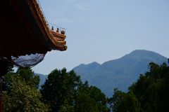 View of wooded Chinese mountains framed by trees and traditional asian roof. Traditional orange ornate Chinese roof framing view of wooded asian mountains. Green stock image