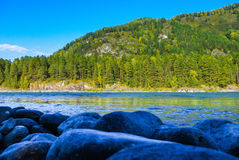 View of the wooded mountain and flowing blue river Royalty Free Stock Images