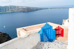 View of wooden blue and red gates and Aegean Sea in Oia, Santorini. Wooden blue and red gates against volcano caldera and Aegean Sea in Oia on Santorini island stock photos