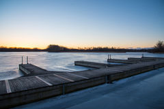 View of wooden boat docks on frozen lake at sunset Royalty Free Stock Images