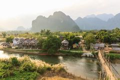 View of wooden bridge over river song, Vang vieng, Laos. View of wooden bridge over river song to riverside guesthouse, Vang vieng, Laos royalty free stock image
