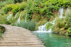 View of wooden deck above green transparent water. With rock behind covered with grass and bushes and several waterfalls in Plitvice Lakes National Park in Royalty Free Stock Photos