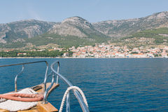 View from the wooden deck of a ship sailing to the rocky shores. Of Croatia, summer, sea, sunny day, Dalmatia Stock Photo