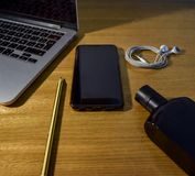 View of wooden desktop with smartphone, laptop, headphones, pencil and perfume. stock photos