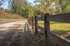 Wooden fence in the shade with dirt road stock photography